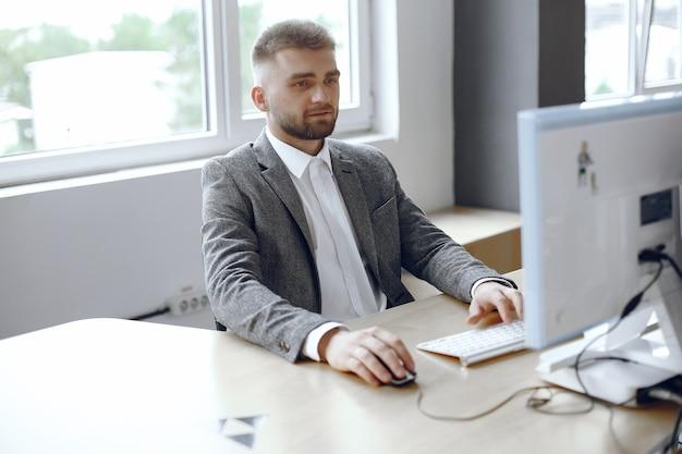 Hombre de negocios que trabaja en la oficina. el hombre usa una computadora. chico está sentado en la oficina Foto gratis
