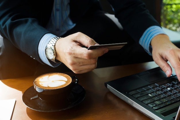 Hombre de negocios que usa la tarjeta de crédito para comprar artículos en línea en la cafetería Foto gratis