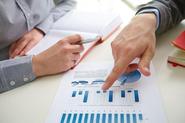 Hombre de negocios señalando un gráfico de barra Foto gratis