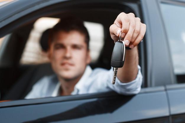 Hombre de negocios sentado en un coche y dando una llave de coche Foto Premium