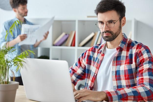 Hombre de negocios serio con barba espesa, analiza tablas y gráficos de ingresos en una computadora portátil, vestido con camisa a cuadros Foto gratis