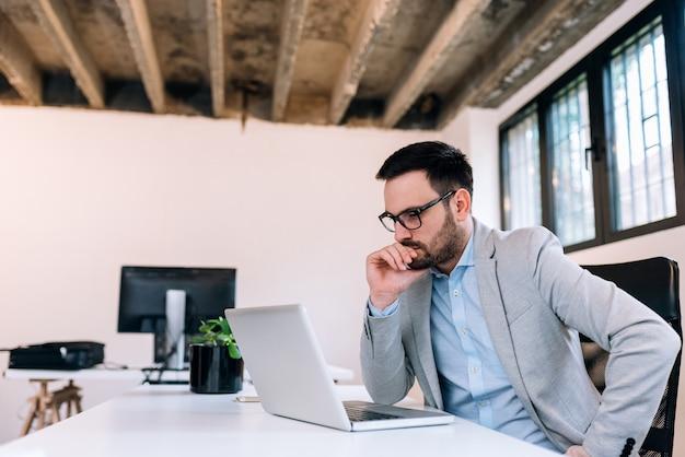 Hombre de negocios serio que mira la pantalla de la computadora portátil. Foto Premium