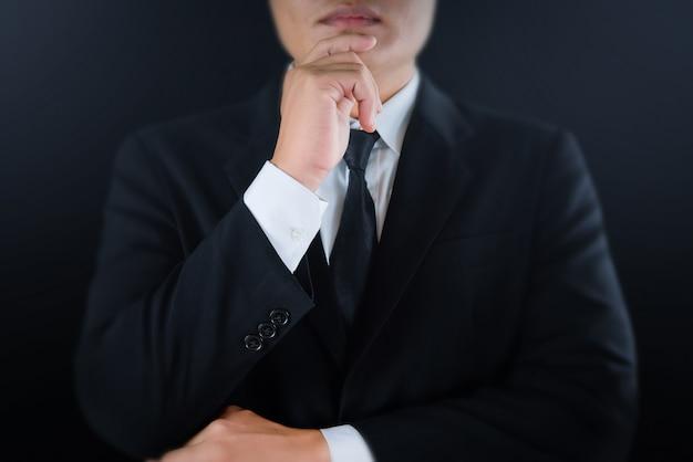 Hombre de negocios serio en traje negro manos tocando la barbilla y mirando. Foto Premium