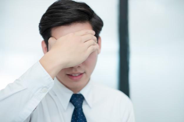 El hombre de negocios siente la cabeza en su corazón mientras trabaja en la oficina, concepto médico Foto Premium