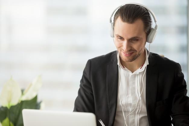 Hombre de negocios sonriente en los auriculares que miran la pantalla de la computadora portátil. Foto gratis