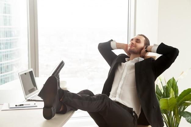 Hombre de negocios sonriente que se relaja en el lugar de trabajo en oficina moderna. Foto gratis