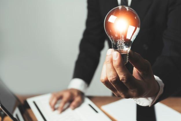 Hombre de negocios sosteniendo una bombilla con monedas dinero y copia espacio para contabilidad, ideas y concepto creativo. Foto Premium