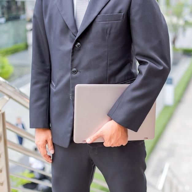 Hombre de negocios con su computadora portátil que sube las escaleras en una hora punta para trabajar. tiempo de prisa Foto Premium