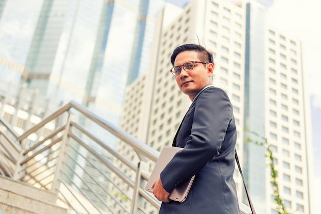 Hombre de negocios con su computadora portátil subiendo las escaleras en una hora pico para trabajar Foto Premium