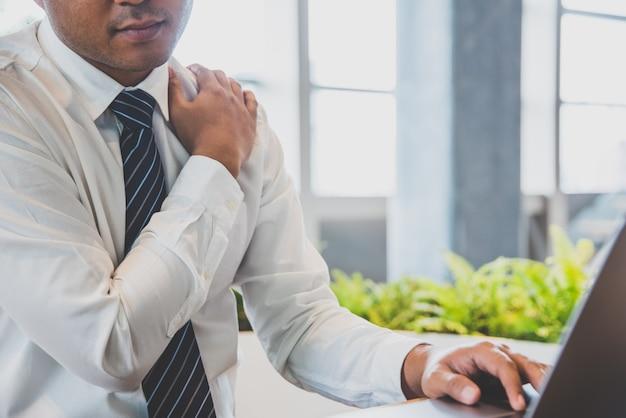 El hombre de negocios tiene dolor de cuello, dolor de hombro mientras trabaja con la computadora portátil. concepto de síndrome de oficina. Foto Premium