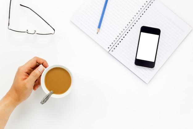 Hombre de negocios tocando la taza de café y teléfono móvil, gafas, café, bloc de notas, lápiz en blanco escritorio de oficina con copia espacio. Foto Premium
