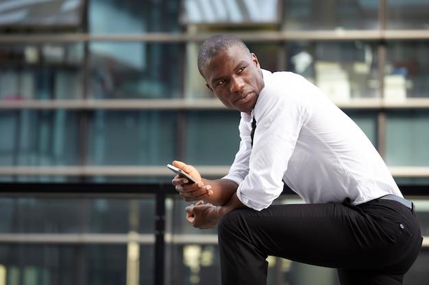 Hombre de negocios trabajando con dispositivos móviles y portátiles en entornos urbanos Foto Premium