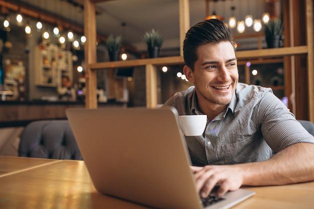 Hombre de negocios trabajando en equipo portátil en un café Foto gratis