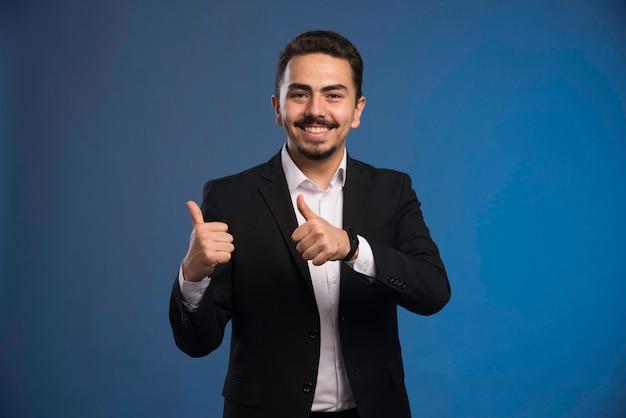 El hombre de negocios en traje negro hace los pulgares para arriba. Foto gratis