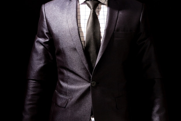 Hombre de negocios con traje negro sobre fondo negro  2120c21395c