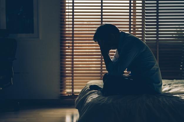 Hombre de negocios triste que se sienta la cabeza en las manos en la cama en el dormitorio oscuro Foto Premium