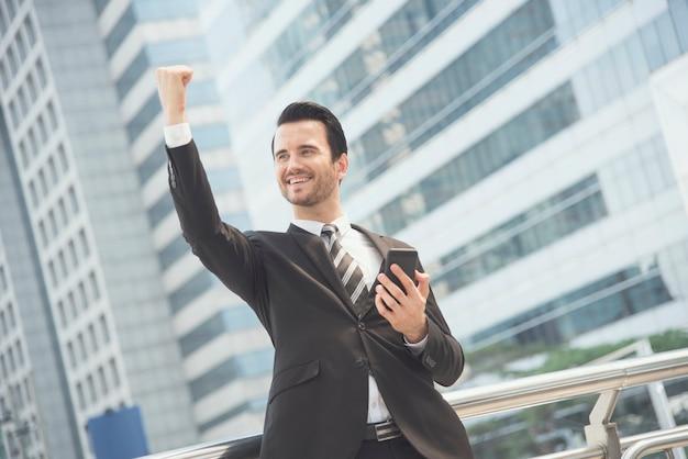 Hombre de negocios usando el teléfono móvil y sonriendo feliz emocionado y levantando su brazo. Foto Premium