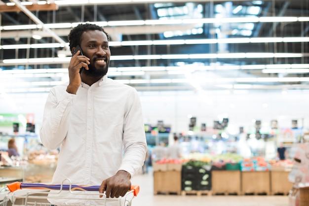 Hombre negro alegre que habla en el teléfono celular en la tienda de comestibles Foto gratis