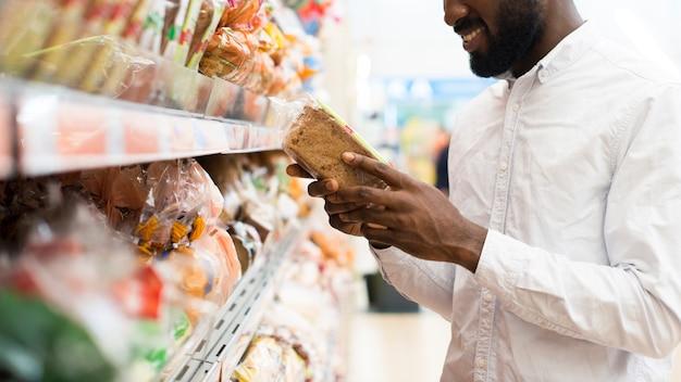 Hombre negro encantado que elige el pan en la tienda de comestibles Foto gratis