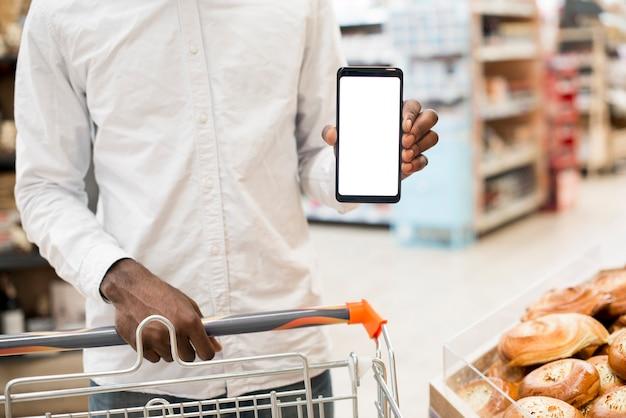 Hombre negro mostrando teléfono inteligente en tienda de comestibles Foto gratis