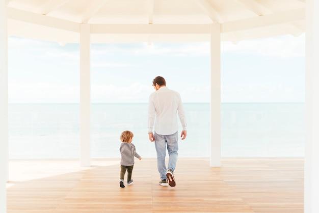 Hombre y niño pequeño caminando en el porche Foto gratis