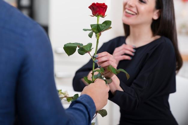Hombre ofreciendo a su novia una rosa para el día de san valentín Foto gratis