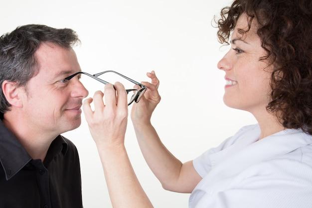 Un hombre en la óptica prueba sus lentes nuevos Foto Premium