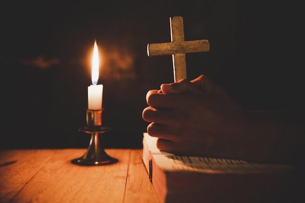 Hombre orando en la biblia en las velas ligeras enfoque selectivo Foto gratis