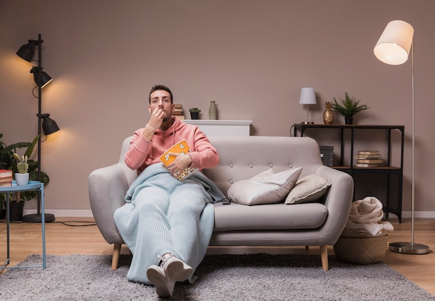 Hombre con palomitas viendo la tele Foto gratis