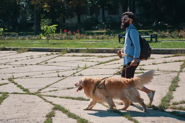 Hombre paseando a su perro en el parque Foto gratis