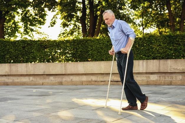 Hombre de paseos en el parque con muletas. el hombre en la terapia. Foto Premium