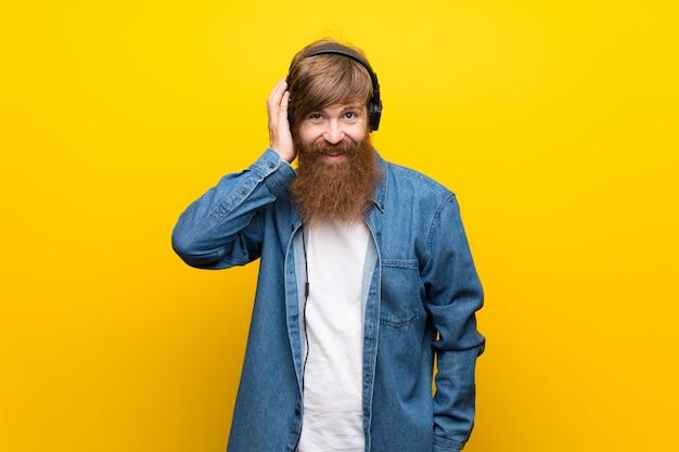 Hombre pelirrojo con barba larga sobre pared amarilla aislada escuchando música con auriculares Foto Premium