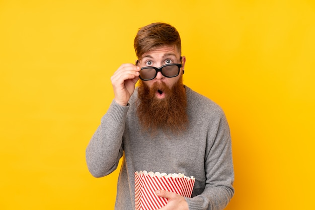 Hombre pelirrojo con barba larga sobre pared amarilla aislada sorprendido con gafas 3d y sosteniendo un gran cubo de palomitas de maíz Foto Premium