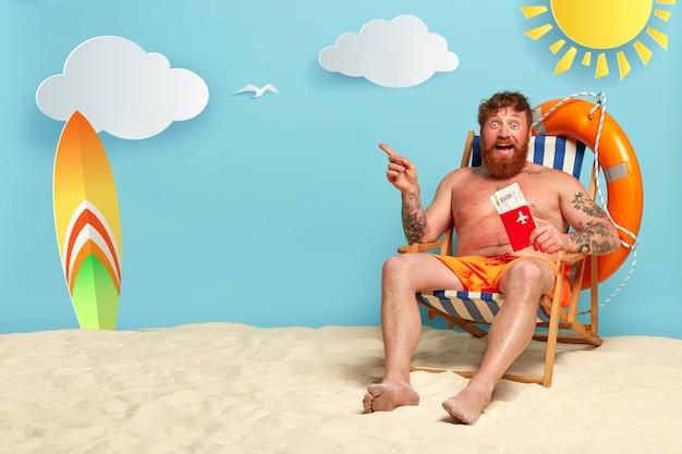 Hombre pelirrojo barbudo topless posando en la playa Foto gratis