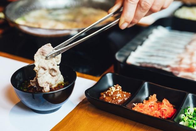 Hombre pellizcando el cerdo kobobuta bien cocido y sumergiéndolo en salsa ponzu con pinzas. Foto Premium