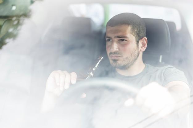 Hombre pensativo con cerveza conduciendo coche Foto gratis