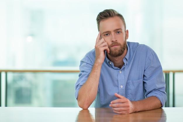 Hombre pensativo joven que se sienta en el vector del café vacía Foto gratis