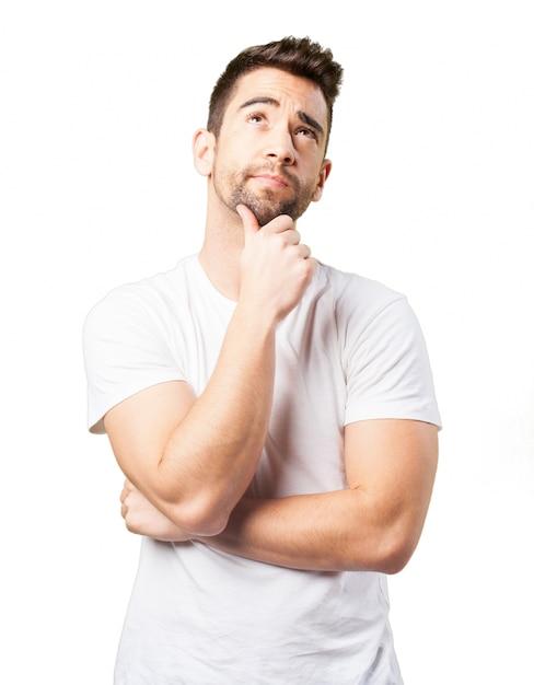 Hombre pensativo con una mano en la barbilla Foto gratis