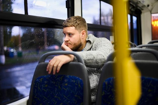 Hombre pensativo mirando por la ventana del autobús Foto gratis