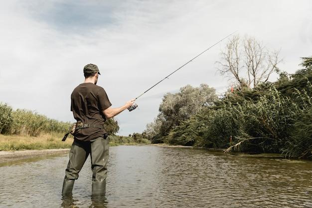 Hombre pescando en el río Foto gratis