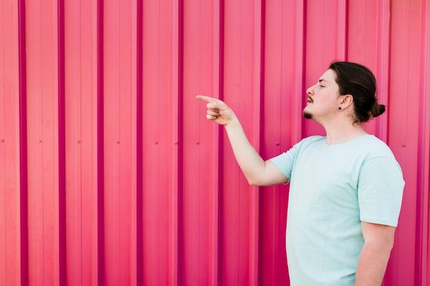 Hombre de pie contra el obturador rojo apuntando el dedo al lado Foto gratis