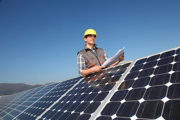 Hombre de pie por paneles solares con plano de construcción. Foto Premium