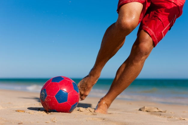 Hombre en la playa jugando al fútbol Foto Premium