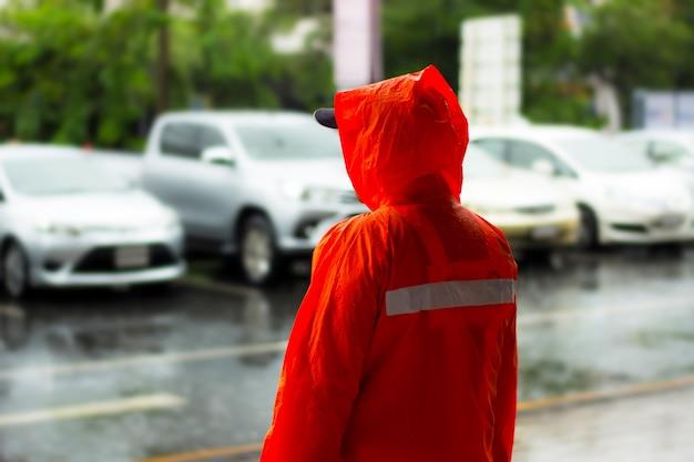 Hombre policía y gabardina naranja soporte medio de la lluvia en el estacionamiento al aire libre Foto Premium
