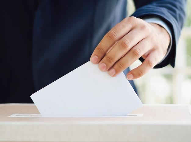 Hombre poniendo una boleta vacía en la casilla electoral Foto gratis