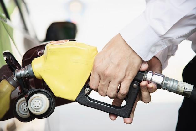 Hombre poniendo combustible de gasolina en su automóvil en una gasolinera de la bomba Foto gratis