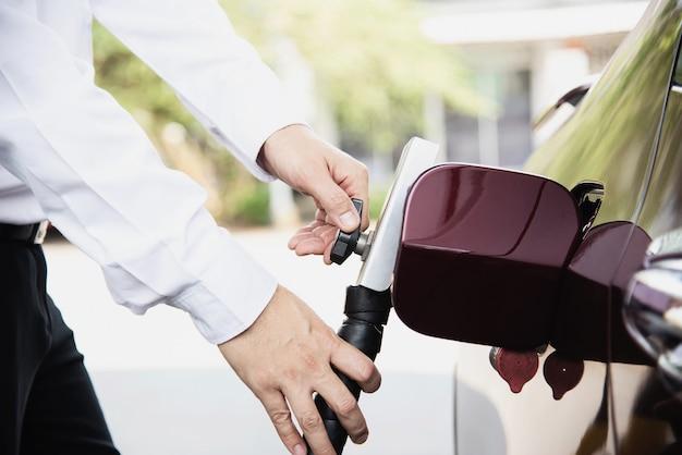 El hombre está poniendo gnv, vehículo de gas natural, dispensador de cabeza a un automóvil en la estación de gasolina en tailandia Foto gratis