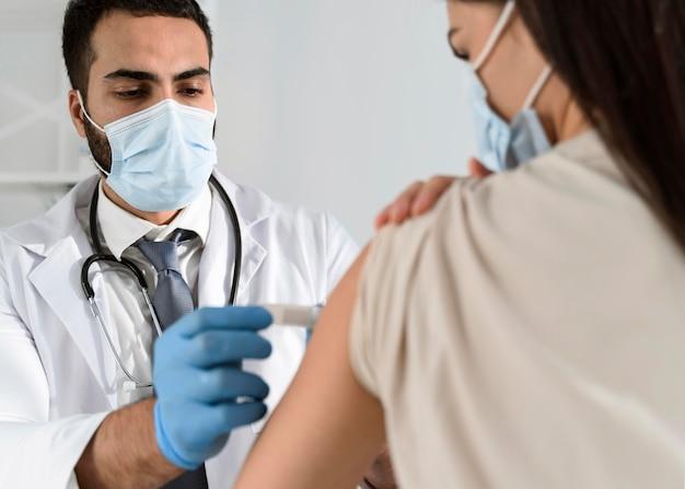 Hombre poniendo un vendaje en el brazo de un paciente Foto gratis