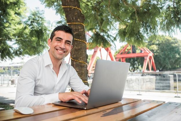 Hombre con portátil al aire libre Foto gratis
