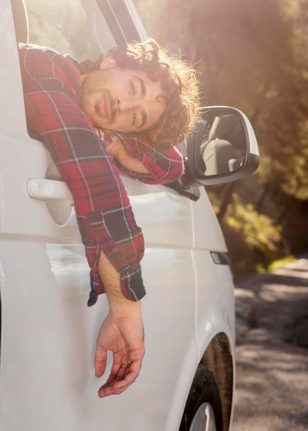 Hombre posando con coche Foto gratis